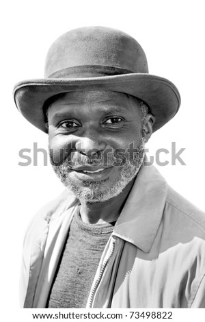 An elderly black man with a scruffy gray beard relaxes at a park on a sunny day. - stock photo
