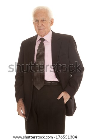 An elderly business man in a suit with his hand in his pocket. - stock photo