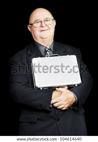 An elderly businessman balances his briefcase confidently on his stomach secure in the wealth of his knowledge, conceptual of business leadership through experience - stock photo