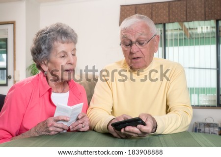 An elderly couple confer as they navigate the instructions for their new phone. - stock photo