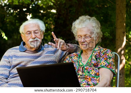 An elderly couple having fun with the laptop in the garden, outside.