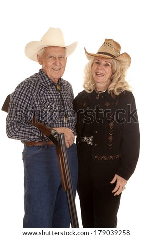 An elderly couple standing by each other while he is holding a shot gun.