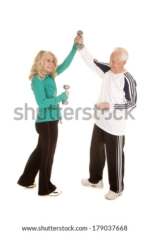 an elderly couple working out and supporting each other in their fitness goals. - stock photo