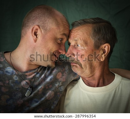 An elderly father and his son smiling and hugging each other. - stock photo