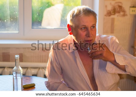 An elderly gray-haired man holding a glass with alcohol sitting at the kitchen table with a bottle of vodka. Social problems: alcoholism