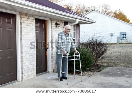 An elderly handicapped man with a walking standing outside his apartment - stock photo