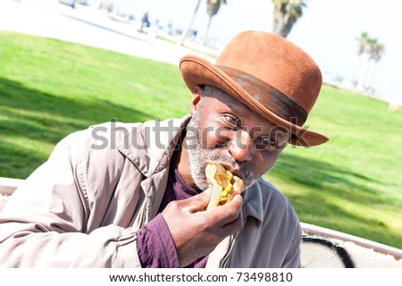 An elderly homeless man eats a hotdog while relaxing in the park. - stock photo