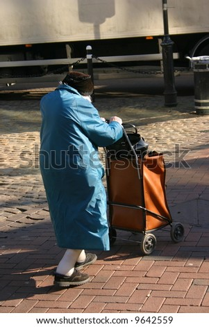 An elderly lady out and about shopping in town - stock photo