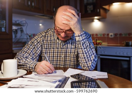 An elderly man calculates the family budget at night. Trying to find a way out of financial problems.