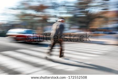An elderly man crosses the street in a crosswalk. Intentional motion blur - stock photo