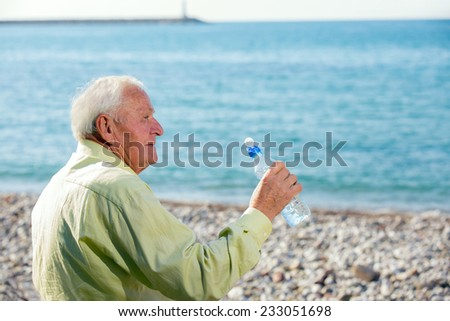 An elderly man drinks water from a bottle and watch the sea - stock photo