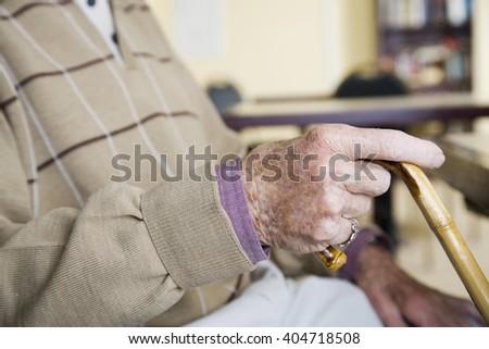 An elderly man holding a walking stick - stock photo