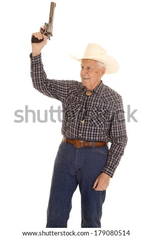 An elderly man in a cowboy hat with a gun in his hand. - stock photo