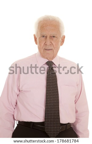 An elderly man in his pink shirt and tie looking serious. - stock photo