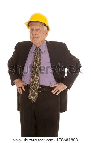 An elderly man in his suit and tie and his construction hat. - stock photo