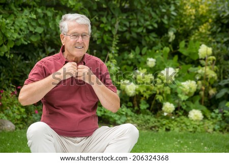 An elderly man is changing his shirt - stock photo