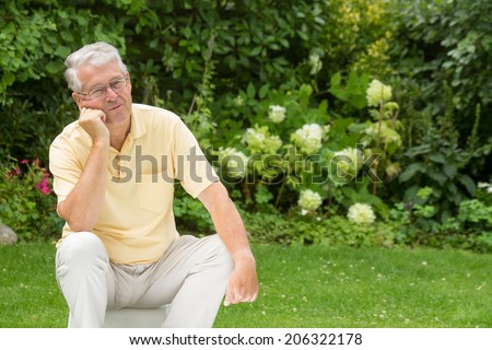 An elderly man is leaning on one knee and bored - stock photo