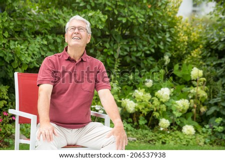 An elderly man is sitting relaxed in a garden while resting his arms on his knees - stock photo