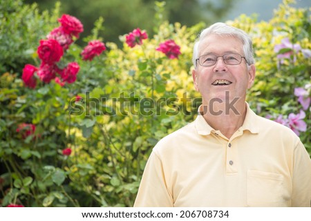 An elderly man is smiling and looking up in front of a beautiful rose background - stock photo
