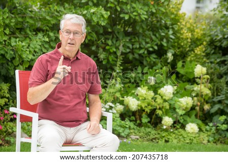 An elderly man is telling you to stop whatever you're doing while looking to the left pensively - stock photo