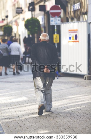 An elderly man is walking in the streets. He is holding his hands behind him. The image is taken from behind and has a vintage effect applied. - stock photo