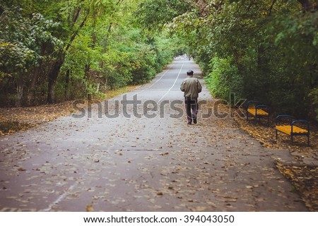 An elderly man is walking trough the park in the early morning. Early autumn. September. Odessa. Solitude. Yellow leaves on the road  - stock photo