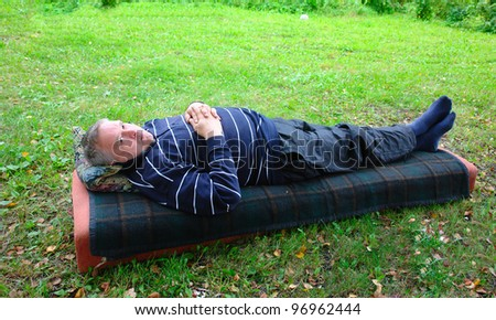 An elderly man lying on a mattress in the woods - stock photo