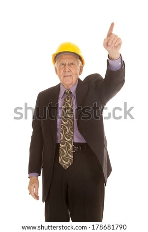 an elderly man pointing his finger up while wearing his hard hat. - stock photo