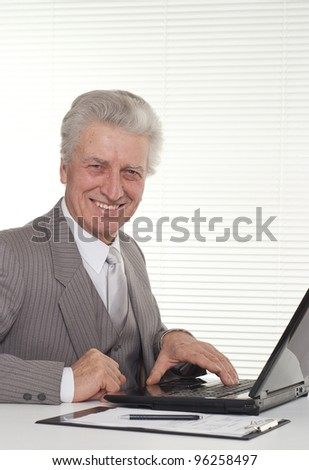 an elderly man sitting at the laptop on a light