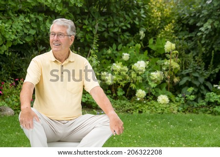 An elderly man sitting looking to the left attentively - stock photo