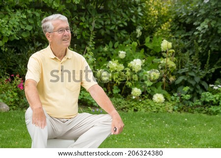 An elderly man sitting looking to the right attentively in a young pose - stock photo