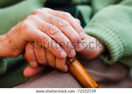 An elderly man sitting, resting his hands on a wooden walking stick. - stock photo