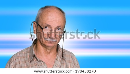 An elderly man with glasses on a blue abstract background - stock photo