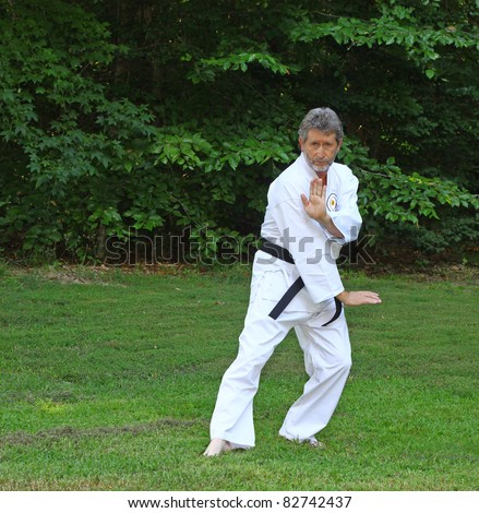 An elderly middle aged Black Belt Martial Artist in his Gi stands ready practicing his Kata outside in his backyard - stock photo