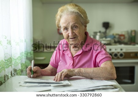 An elderly woman fills the bill for utilities sitting in the kitchen.