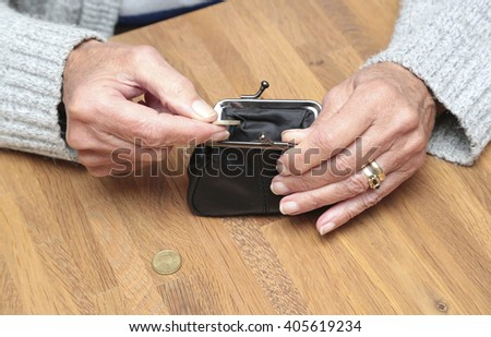 An elderly woman gets some money from her purse - stock photo