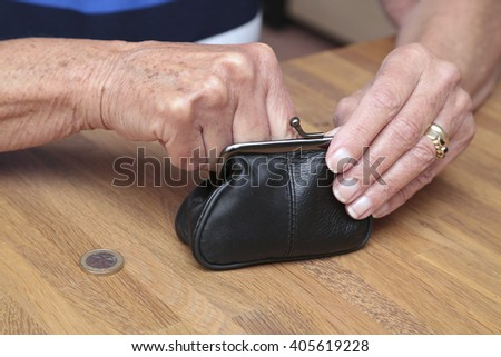 An elderly woman gets some money from her wallet - stock photo
