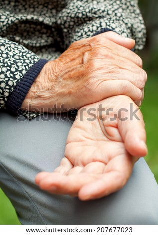 An elderly woman holding her painful wrist
