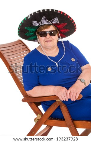 An elderly woman in a wide-brimmed hat, and sunglasses resting, sitting in a lawn chair, isolated on white background