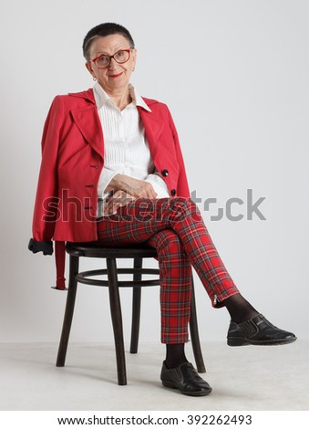 An elderly woman in red glasses sitting on a chair .