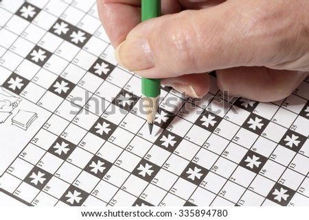 An elderly woman is doing crossword puzzle with a pencil. This is a good exercise for older people to train their brains. - stock photo