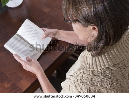 An elderly woman is reading a book on a kitchen table. Image taken against a wooden table and indoor.