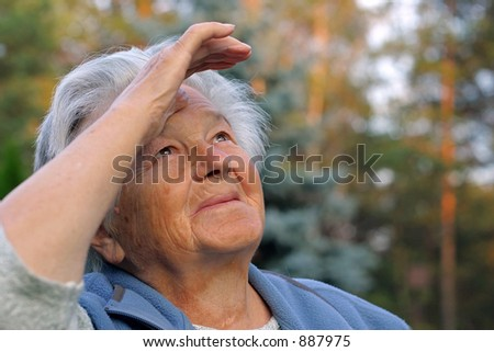 an elderly woman looking into the sky.