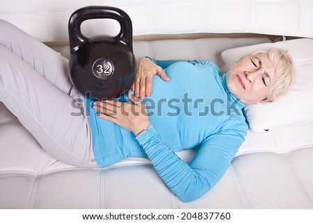 An elderly woman lying on the sofa with abdominal pain and weight. - stock photo