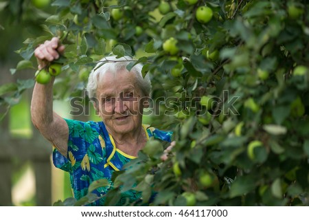 An elderly woman near Apple tree in the garden.