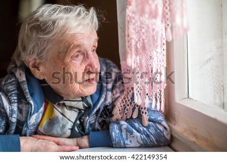 An elderly woman near the window. - stock photo