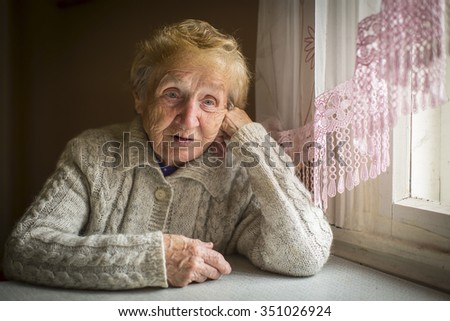 An elderly woman sits alone near the window. - stock photo