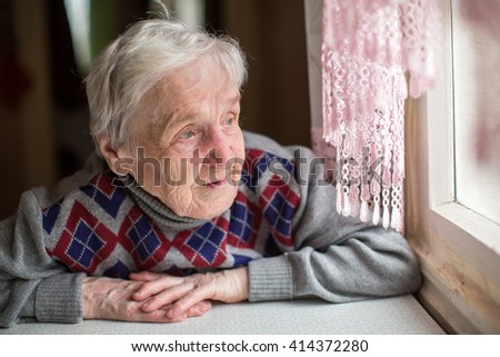 An elderly woman sits and looking out the window. - stock photo