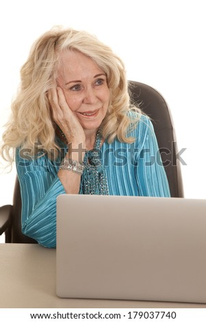 An elderly woman sitting at her desk not wanting to work on her laptop.