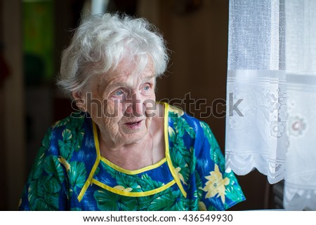 An elderly woman sitting at the table looking out the window. - stock photo